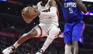 Miami Heat guard Dwyane Wade, left, passes the ball as Los Angeles Clippers forward Montrezl Harrell defends during the second half of an NBA basketball game, Saturday, Dec. 8, 2018, in Los Angeles. The Heat won 121-98. (AP Photo/Mark J. Terrill)