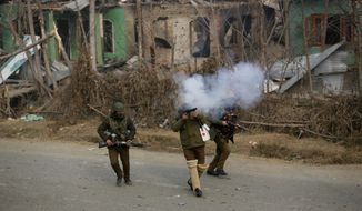 An Indian policeman fires a tear gas shell towards Kashmiri protesters near the site of a gun-battle in Mujagund area some 25 Kilometers (16 miles) from Srinagar, Indian controlled Kashmir, Sunday, Dec. 9, 2018. Indian troops killed three suspected rebels in the outskirts of disputed Kashmir's main city ending nearly 18-hour-long gunbattle, officials said Sunday. (AP Photo/Mukhtar Khan)