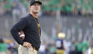 FILE - In this Sept. 1, 2018, file photo, Michigan coach Jim Harbaugh stands on the field before the team's NCAA college football game against Notre Dame in South Bend, Ind. Harbaugh says he is staying at Michigan, responding to speculation he's returning to the NFL. The former San Francisco 49ers coach tells ESPN he's not going anywhere. Fox Sports analyst Cris Carter has said Harbaugh is a potential candidate to lead Green Bay and Cleveland. Michigan won 10 games this season for the third time under Harbaugh but dropped to 0-4 against rival Ohio State. (AP Photo/Paul Sancya, File)