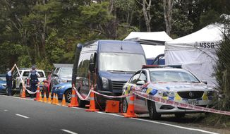 Police man a cordon along a section of Scenic Drive in the Waitakere Ranges outside Auckland, New Zealand, Sunday, Dec. 9, 2018. New Zealand police said Saturday, Dec. 8, that they believe a 22-year-old British tourist who has been missing for a week was murdered, and they will lay charges against a man they detained earlier in the day for questioning. (Doug Sherring/NZ Herald via AP)