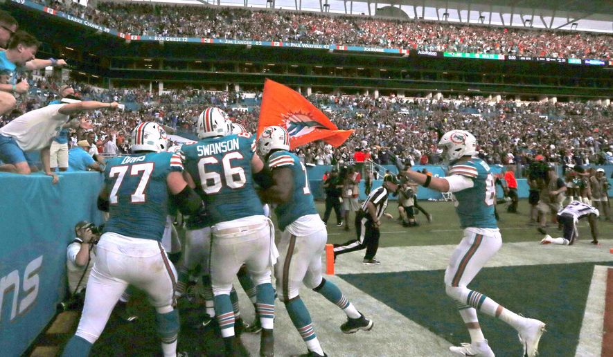 The Miami Dolphins celebrate with running back Kenyan Drake after he scored the winning touchdown during fourth quarter of an NFL football game against the New England Patriots Sunday, Dec. 9 2018, in Miami Gardens. The Dolphins won 34-33. (David Santiago/Miami Herald via AP)