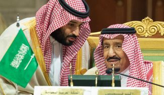 In this photo released by the state-run Saudi Press Agency, Saudi Crown Prince Mohammed bin Salman, left, speaks to his father, King Salman, right, at a meeting of the Gulf Cooperation Council in Riyadh, Saudi Arabia, Sunday, Dec. 9, 2018. Leaders of Gulf Arab countries, including those boycotting Qatar, met on Sunday in Saudi Arabia's capital for a regional summit, a gathering that Qatar's ruling emir choose not to attend amid the dispute. (Saudi Press Agency via AP)