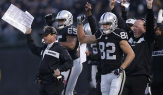 Oakland Raiders head coach Jon Gruden, left, celebrates with players and coaches after a touchdown against the Pittsburgh Steelers during the second half of an NFL football game in Oakland, Calif., Sunday, Dec. 9, 2018. (AP Photo/D. Ross Cameron)