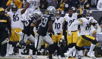 Pittsburgh Steelers wide receiver JuJu Smith-Schuster (19) runs in front of Oakland Raiders linebacker Tahir Whitehead (59) and defensive back Erik Harris (25) during the second half of an NFL football game in Oakland, Calif., Sunday, Dec. 9, 2018. (AP Photo/D. Ross Cameron)