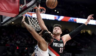 Portland Trail Blazers center Jusuf Nurkic, right, blocks the shot of Minnesota Timberwolves guard Derrick Rose during the first half of an NBA basketball game in Portland, Ore., Saturday, Dec. 8, 2018. (AP Photo/Steve Dykes)