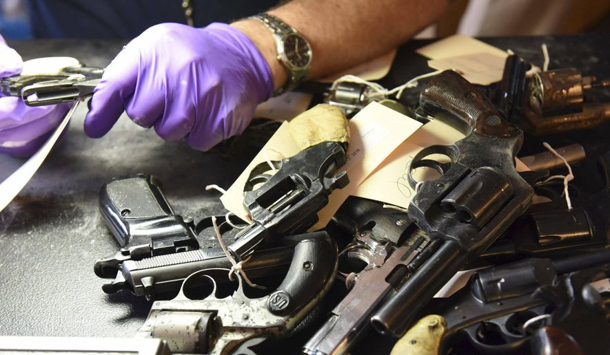 In this June 2, 2018, photo provided by the Chicago Police Department, forensic firearms examiners inspect weapons turned in by residents in a gun buy-back program co-sponsored with the New Life Covenant Church Southeast in the 6th Police District. More than 400 guns and rifles were handed over in exchange for $100 gift cards. (CPD via AP) **FILE**