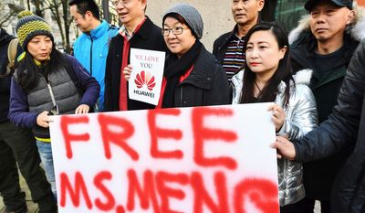 People hold a sign at a Vancouver, British Columbia, courthouse prior to the bail hearing for Meng Wanzhou, Huawei's chief financial officer on Monday. (Associated Press)