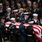 The flag-draped casket of former President George H.W. Bush is carried by a military honor guard past former presidents and first ladies George W. Bush and wife Laura Bush, President Donald Trump, first lady Melania Trump, former President Barack Obama, Michelle Obama, former President Bill Clinton, former Secretary of State Hillary Clinton and former President Jimmy Carter during a State Funeral at the National Cathedral, Wednesday, Dec. 5, 2018, in Washington. (AP Photo/Carolyn Kaster)