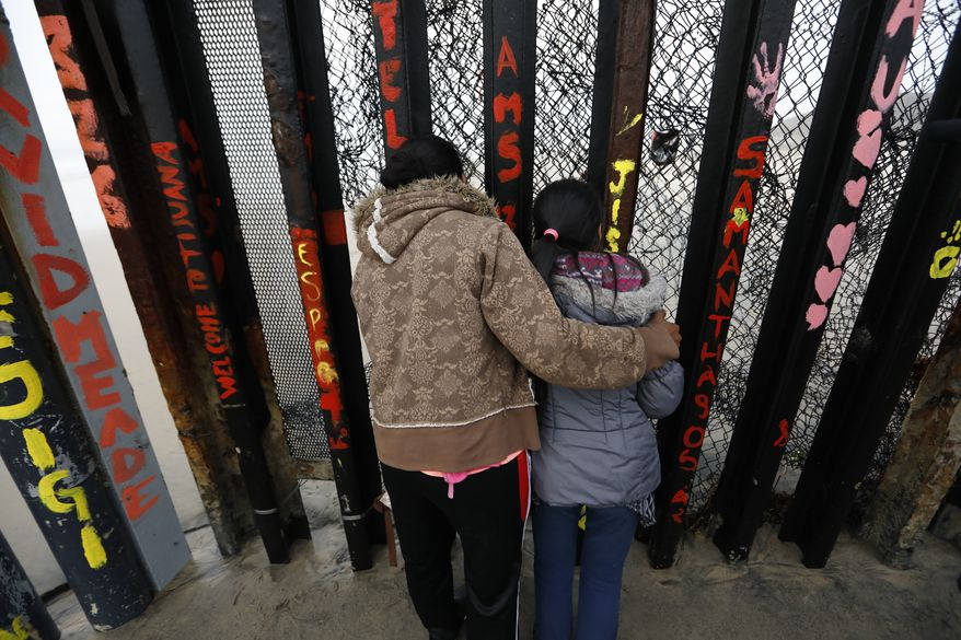 A Honduran migrant and her daughter peer through the U.S. border wall, moments before suddenly squeezing through a gap and pushing through fencing to exit on the U.S. side, in Tijuana, Mexico, Sunday, Dec. 9, 2018. Discouraged by the long wait to apply for asylum through official ports of entry, many Central American migrants from recent caravans are choosing to cross the U.S. border wall illegally and hand themselves in to Border Patrol agents to request asylum. (AP Photo/Rebecca Blackwell)