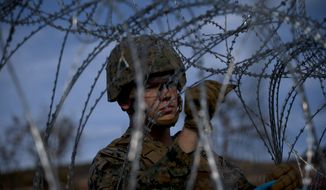 """A soldier agent sets up barbed wire at the San Ysidro port of entry, at the U.S.-Mexico border, seen from Tijuana, Mexico, Thursday, Nov. 22, 2018. U.S. President Donald Trump threatened Thursday to close the U.S. border with Mexico for an undisclosed period if his administration determines Mexico has lost """"control"""" on its side. (AP Photo/Ramon Espinosa)"""