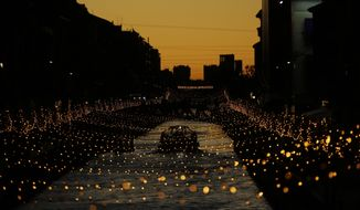 A boat sail along the Naviglio canal decorated with Christmas lights, in Milan, Italy, Monday, Dec. 10, 2018. (AP Photo/Luca Bruno)