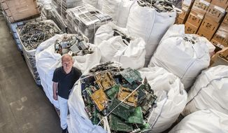 In this photo taken on July 13, 2018, founder of the company, Out Of Use, Mark Adriaenssens, stands among bags of electronic parts and components to be recycled at his warehouse in Beringen, Belgium. European Union nations are expected to produce more than 12 million tons of electronic waste per year by 2020, putting the Out Of Use company at the front of an expanding market, recuperating raw materials from electronic waste. (AP Photo/Geert Vanden Wijngaert)