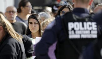 FILE - In this Nov. 19, 2018, file photo, people line up to cross into the United States from Tijuana, Mexico, at the San Ysidro port of entry in San Diego. U.S. immigration authorities say the number of people expressing fear of returning home when they are stopped at the Mexican border spiked in the last year. (AP Photo/Gregory Bull, File)