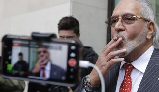 Indian business man Vijay Mallya is filmed by the media as he takes a smoking break outside Westminster Magistrates Court in London, Monday, Dec. 10, 2018. A British judge is expected to rule on whether wealthy Indian entrepreneur Vijay Mallya will be extradited to India to face fraud allegations. (AP Photo/Kirsty Wigglesworth)