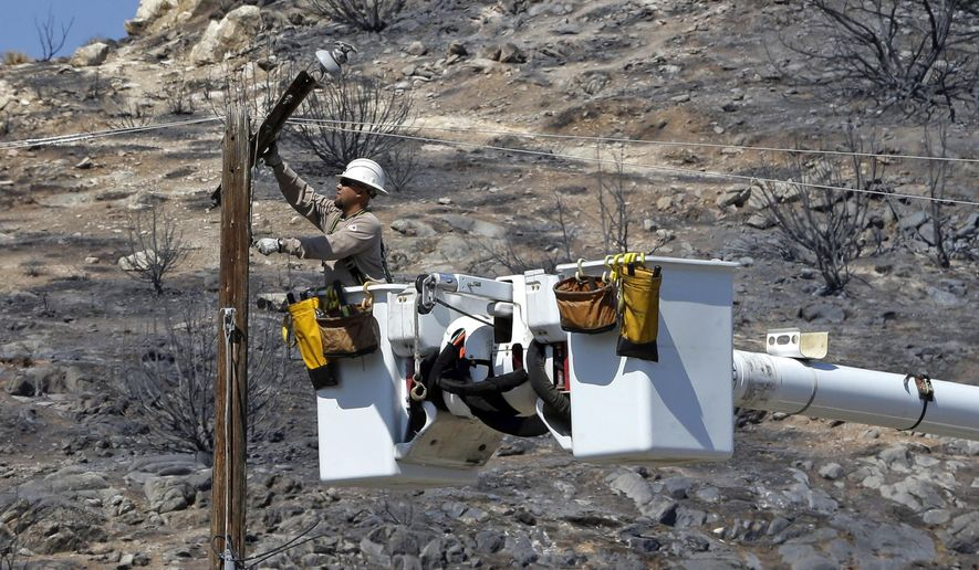 FILE - In this June 27, 2016 file photo, Robert Delgado, a lineman for Southern California Edison, works on a power line at fire ravaged South Lake, Calif. SCE wants to spend $582 million to cover some power lines and deploy cameras in areas at high risk for wildfires. Officials from the utility shared plans with legislative staff on Monday, Dec. 10, 2018 as the utility works on clean up and repair from the Woolsey Fire last month. (AP Photo/Rich Pedroncelli, File)