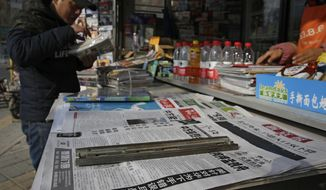 A man arranges magazines near newspapers with the headlines of China outcry against U.S. on the detention of Huawei's chief financial officer, Meng Wanzhou, at a news stand in Beijing, Monday, Dec. 10, 2018. China has summoned the U.S. ambassador to Beijing to protest Canada's detention of an executive of Chinese electronics giant Huawei at Washington's behest and demand the U.S. cancel an order for her arrest. (AP Photo/Andy Wong)