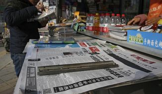 A man arranges magazines near newspapers with the headlines of China outcry against the U.S. on the detention of Huawei's chief financial officer, Meng Wanzhou. (Associated Press/File)