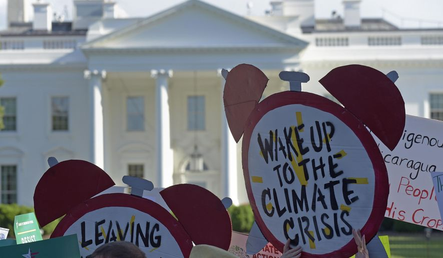 FILE - In this June 1, 2017 file photo, protesters gather outside the White House in Washington to protest President Donald Trump's decision to withdraw the Unites States from the Paris climate change accord. Environmental activists are ramping up a pressure campaign aimed at stoking Democratic support for an ambitious environmental plan known as the Green New Deal ahead of the 2020 presidential race.  (AP Photo/Susan Walsh)