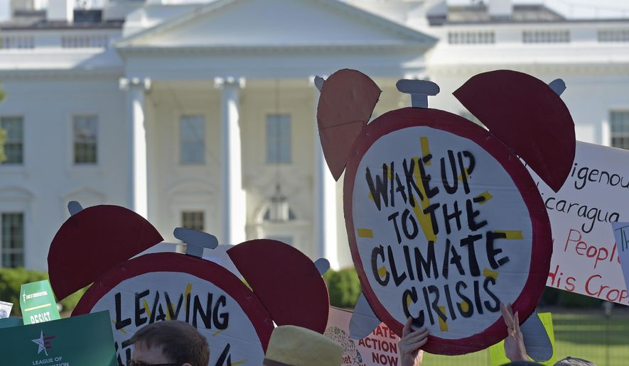 In this June 1, 2017 file photo, protesters gather outside the White House in Washington to protest President Donald Trump's decision to withdraw the Unites States from the Paris climate change accord. On March 28, 2019, the first meeting of a new House Select Committee on the Climate Crisis convened, a new congressional panel established by the Democratic Congress to work on climate-change legislative issues. (AP Photo/Susan Walsh)