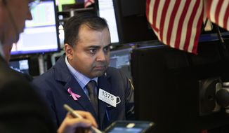 Specialist Dilip Patel works at the New York Stock Exchange, Monday, Dec. 10, 2018. Stocks are wobbling between small gains and losses in the early going on Wall Street as trading settles down following huge losses last week. (AP Photo/Mark Lennihan)