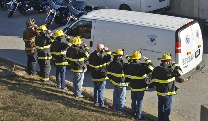 Firefighters salute as the Medical Examiner's transports the body of Worcester firefighter Christopher Roy Monday, Dec. 10, 2018 in Worcester, Mass. Roy was killed Sunday fighting a 5-alarm fire in Worcester. (Chris Christo/The Boston Herald via AP)