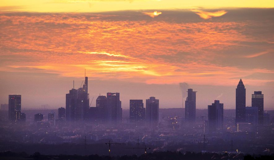 The sun is about to rise over the buildings of the banking district in Frankfurt, Germany, Wednesday, Dec. 5, 2018. (AP Photo/Michael Probst)