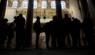 In this Thursday, Dec. 6, 2018 photo, visitors stand bellow a renovated part of a fresco inside the Church of the Nativity, built atop the site where Christians believe Jesus Christ was born, in the West Bank City of Bethlehem. City officials are optimistic that the renovated church will help add to a recent tourism boom and give a boost to the shrinking local Christian population. (AP Photo/Majdi Mohammed)