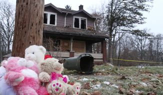 Stuffed animals rest against a pole at a makeshift memorial after a deadly fire in Youngstown, Ohio, Monday, Dec. 10, 2018. Authorities report that several children died in the fire. (William D. Lewis/The Vindicator via AP)