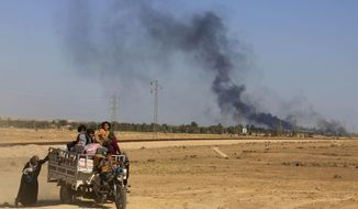 In this Monday, April 4, 2016, file photo, smoke rises as people flee their homes during clashes between Iraqi security forces and members of the Islamic State group in Hit, Iraq, 85 miles (140 kilometers) west of Baghdad, Iraq. Iraq on Monday, Dec. 10, 2018, celebrated the anniversary of its costly victory over the Islamic State group, which has lost virtually all the territory it once held but still carries out sporadic attacks. (AP Photo/Khalid Mohammed, File)