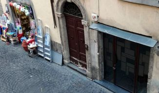 A hole in the cobblestone pavement is seen where 20 small bronze plaques honoring the members of a Jewish family deported during the Holocaust should have been, in Rome's Monti neighborhood, Monday, Dec. 10, 2018.. The plaques, affixed to the cobblestones in front of the Di Consiglio family home, were apparently taken overnight. Rome's historic center houses the Jewish ghetto, near Monti, and its cobblestoned streets are dotted with the plaques in front of homes of Jews who were killed or deported. (Silvia Lambertucci/ANSA via AP)