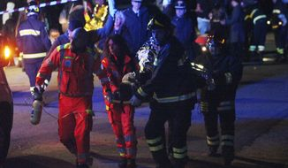Rescuers assist injured people outside disco Lanterna Azzurra in Corinaldo, central Italy, Saturday, Dec. 8, 2018. A stampede at a rap concert in an overcrowded disco in central Italy killed five young teenagers and a woman who had accompanied her daughter to the event early Saturday, police said, adding that 59 people were injured. (AP Photo/Bobo Antic)