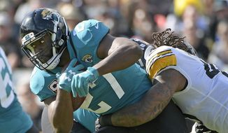 FILE - In this Nov. 18, 2018, file photo, Jacksonville Jaguars running back Leonard Fournette, left, runs for yardage as he is stopped by Pittsburgh Steelers outside linebacker Bud Dupree, right, during the first half of an NFL football game in Jacksonville, Fla. Jaguars coach Doug Marrone says Fournette was responding to racial slurs while yelling at a fan in Nashville, Tenn., last Thursday, Dec. 6, 2018. Fournette declined to address the accusation in the locker room Monday, Dec. 10, 2018, on the advice of his agent. (AP Photo/Phelan M. Ebenhack) ** FILE **