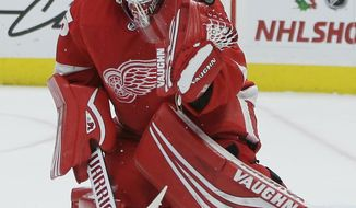 A shot deflects off the shoulder of Detroit Red Wings goaltender Jimmy Howard (35) during the first period of an NHL hockey game against the Los Angeles Kings, Monday, Dec. 10, 2018, in Detroit. (AP Photo/Duane Burleson)