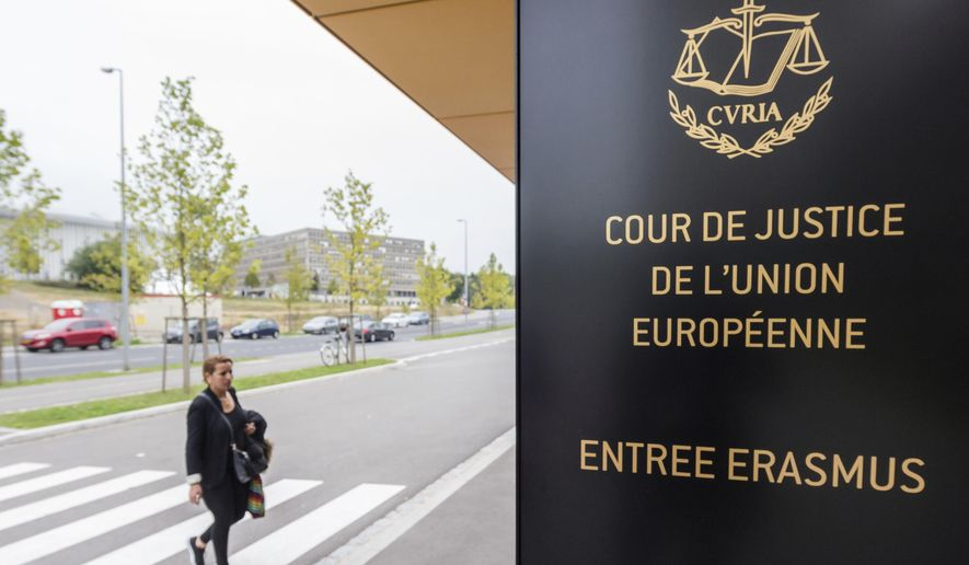 In this file photo taken on Monday, Oct. 5, 2015 a woman walks by the entrance to the European Court of Justice in Luxembourg. (AP Photo/Geert Vanden Wijngaert)  **FILE**
