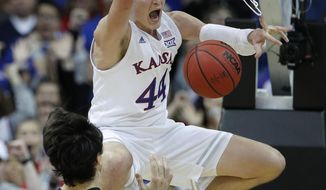Kansas' Mitch Lightfoot (44) celebrates after getting past New Mexico State's Ivan Aurrecoechea (15) for a dunk during the second half of an NCAA college basketball game Saturday, Dec. 8, 2018, in Kansas City, Mo. Kansas won 63-60. (AP Photo/Charlie Riedel)