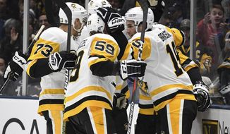 Pittsburgh Penguins players celebrate a goal by center Derick Brassard (19) during the third period of an NHL hockey game against the New York Islanders, Monday, Dec. 10, 2018, in Uniondale, N.Y. (AP Photo/Kathleen Malone-Van Dyke)