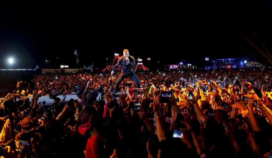 FILE - In this Nov. 18, 2018, file photo, Dan Reynolds, center, of the band Imagine Dragons performs on the second day of the Corona Capital music festival in Mexico City. Grammy Award winners Imagine Dragons will perform at halftime of the College Football Playoff championship game on Jan. 7, 2019. ESPN and Interscope Records announced the performance Monday, Dec. 10, 2018. (AP Photo/Eduardo Verdugo, File)