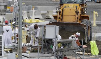 """In this March 6, 2013, file photo, workers are shown at the """"C"""" Tank Farm at the Hanford Nuclear Reservation, near Richland, Wash. Conservation groups are alarmed by the Trump administration's proposal to rename some radioactive waste left from the production of nuclear weapons to make it cheaper and easier to achieve permanent disposal. The U.S. Department of Energy is considering a change in its legal definition of high-level radioactive waste, which is stored at places like the Hanford. (AP Photo/Ted S. Warren, File)"""