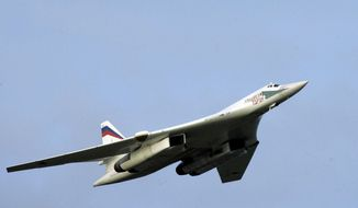 FILE - In this Tuesday, Aug. 16, 2005 file photo, a supersonic Tu-160 strategic bomber with Russian President Vladimir Putin aboard flies above an airfield near the northern city of Murmansk. The Russian military says two of its nuclear-capable strategic bombers have arrived in Venezuela, a deployment that comes amid soaring Russia-U.S. tensions. (Alexei Panov, Sputnik, Kremlin Pool Photo via AP, File)