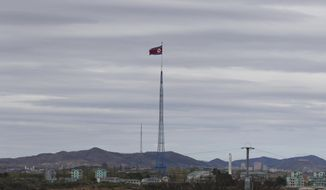 FILE - In this April 27, 2018, file photo, a North Korean flag flutters in the wind atop a 160-meter tower in North Korea's village Gijungdongseen, as seen from the Taesungdong freedom village inside the demilitarized zone in Paju, South Korea. South Korean prosecutors on Monday, Dec. 10, 2018, have charged four people with illegally importing North Korean coal via Russia in violation of U.N. sanctions. (AP Photo/Lee Jin-man, File)