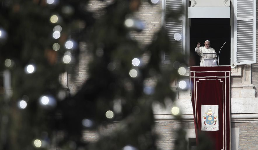 Framed by a Christmas tree, Pope Francis waves during the Angelus noon prayer from his studio window overlooking St. Peter's Square at the Vatican, Sunday, Dec. 9, 2018. (AP Photo/Alessandra Tarantino)