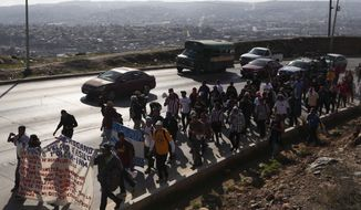 Central American migrants march to the U.S. consulate in Tijuana, Mexico, Tuesday, Dec. 11, 2018. Migrants want U.S. authorities to speed up the asylum application process for members of migrant caravans seeking to enter the U.S., including accepting more applications per day. (AP Photo/Moises Castillo)