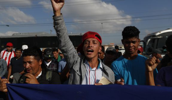 A Honduran migrant chants slogans during a demonstration outside the U.S. consulate in Tijuana, Mexico, Tuesday, Dec. 11, 2018. Migrants want U.S. authorities to speed up the asylum application process for members of migrant caravans seeking to enter the U.S., including accepting more applications per day. (AP Photo/Moises Castillo)
