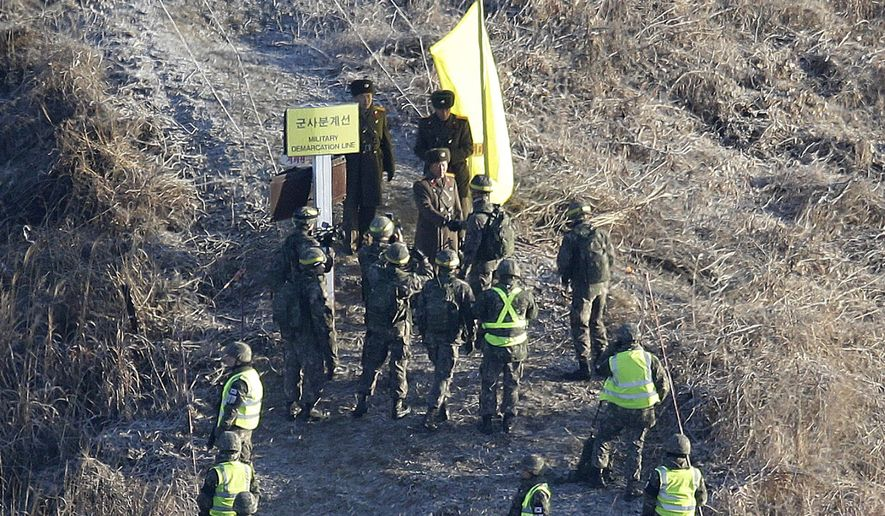 A South Korean army soldier, center bottom, shakes hands with a North Korean army soldier before crossing the Military Demarcation Line inside the Demilitarized Zone (DMZ) to inspect the dismantled North Korean guard post in the central section of the inter-Korean border in Cheorwon, Wednesday, Dec. 12, 2018. South Korea and North Korea have removed some of their guard posts along the border as part of their military agreement last September. (AP Photo/Ahn Young-joon, Pool)