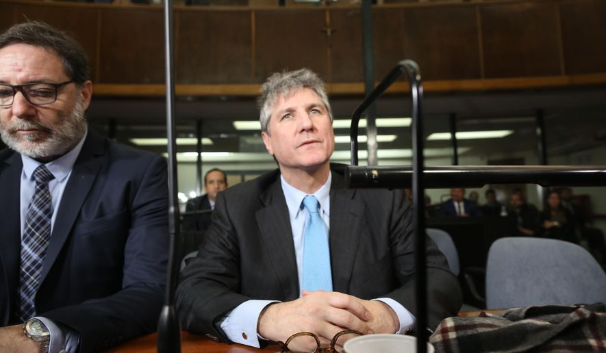 FILE - In this Aug. 7, 2018 file photo, Argentina's former Vice President Amado Boudou, right, and his lawyer Alejandro Rua sit in court in Buenos Aires, Argentina before Boudou was sentenced to five years and 10 months in prison for bribery and conducting business incompatible with public office. On Tuesday, Dec. 11, 2018, a court in Argentina released Boudou from prison under bail, saying that the sentence is not firm since it is still being appealed. (AP Photo/Sebastian Pani, File)