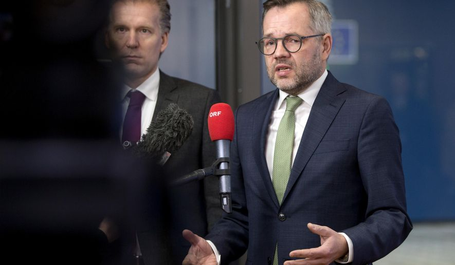 German Minister of State for European Affairs Michael Roth, right, speaks with the media as he arrives for a General Affairs Council meeting at the Europa building in Brussels, Tuesday, Dec. 11, 2018. Top European Union officials ruled out Tuesday any renegotiation of the divorce agreement with Britain as Prime Minister Theresa May launched her fight to save her Brexit deal by lobbying leaders in Europe's capitals. (AP Photo/Virginia Mayo)