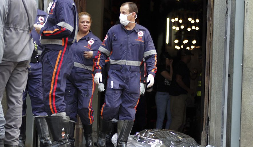A firefighter walks next to a victim killed at the Metropolitan Cathedral in Campinas, Brazil, Tuesday, Dec.11, 2018. Authorities say an armed man entered the cathedral in southern Brazil on Tuesday afternoon and opened fire, killing at least four people before killing himself. (Denny Cesare/Futura Press via AP)