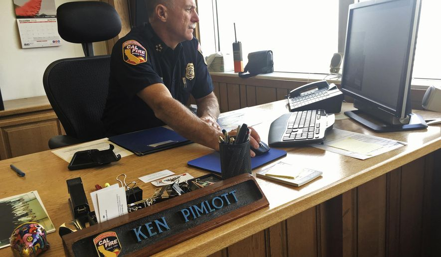 In this photo taken Monday, Dec. 10, 2018, California Department of Forestry and Fire Protection Director Ken Pimlott works at his desk in his office in Sacramento, Calif. Pimlott told The Associated Press he prepares to retire on Friday, Dec. 14, 2018, after a 30-year career. (AP Photo/Haven Daley)