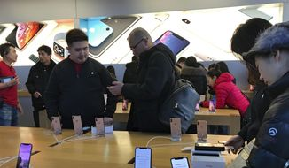 People buy the latest iPhone while others try out its latest model at an Apple Store in Beijing, Tuesday, Dec. 11, 2018. (AP Photo/Andy Wong) ** FILE **