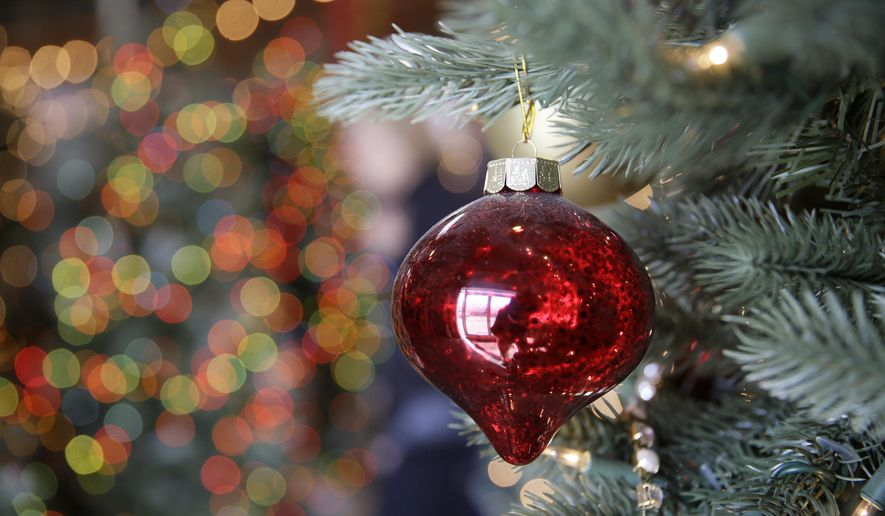 In this Friday, Nov. 30, 2018, photo, an ornament hangs on an artificial Christmas tree at the Balsam Hill Outlet store in Burlingame, Calif. (AP Photo/Eric Risberg) ** FILE **